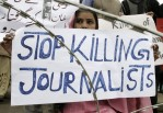 Journalist holds a placard during a protest against the killing of a journalist in Swat Valley
